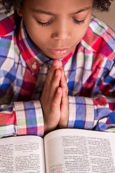 Menino mulato rezando. garoto de camisa está rezando. jovem com livro de orações. sua fé é forte.