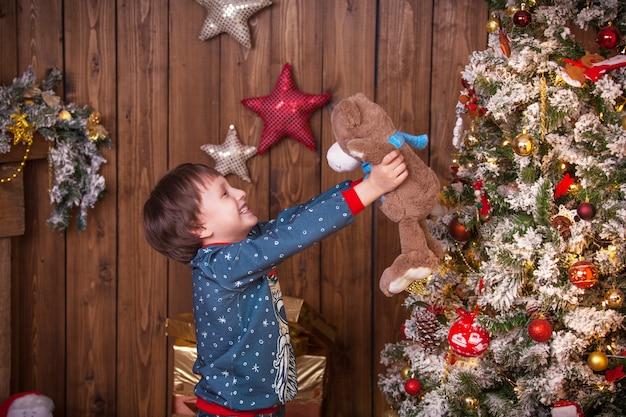 Menino na árvore de natal com presentes