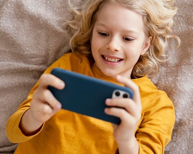Menino na cama brincando no celular
