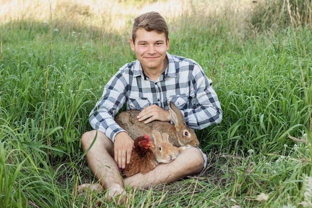Menino na grama brincando com coelhos e frango