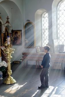Menino na igreja ortodoxa com uma bela luz do sol na janela