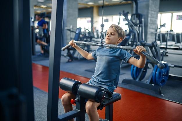 Menino na máquina de exercícios, treinando na academia. jovem em um clube esportivo, saúde e estilo de vida saudável, estudante em exercício, juventude esportiva