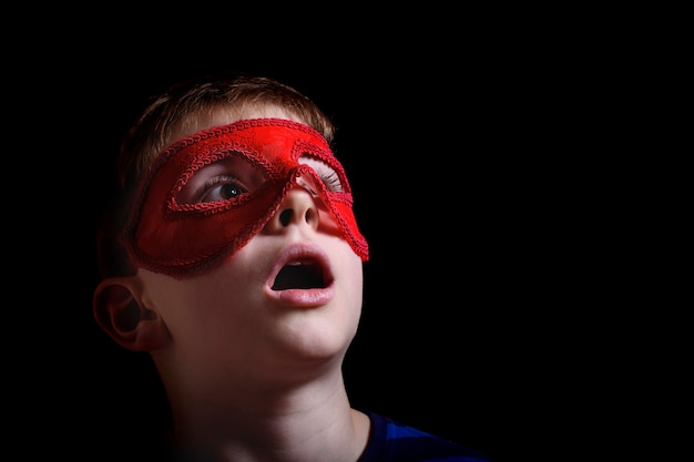 Menino na máscara de carnaval vermelho no preto. closeup retrato isolado.