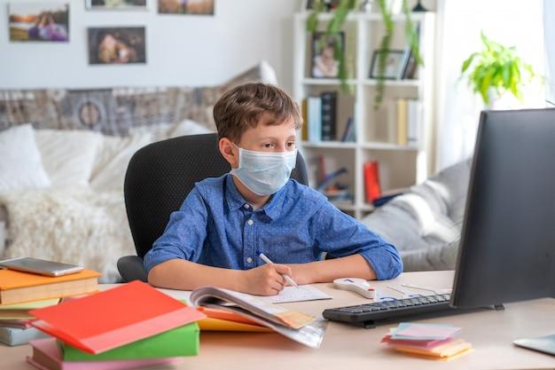 Menino na máscara facial usando o computador, fazendo lição de casa durante a quarentena de coronavírus