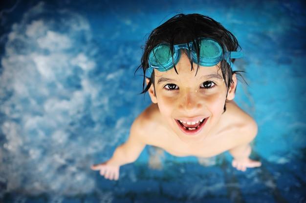 Menino na piscina com óculos