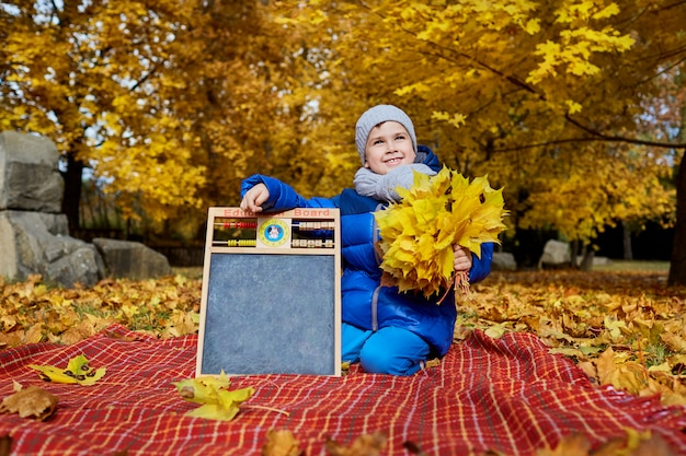 Menino na roupa brilhante com as folhas em suas mãos ao lado da educação, placa em um parque no outono fora. o conceito de crianças, educação, queda.