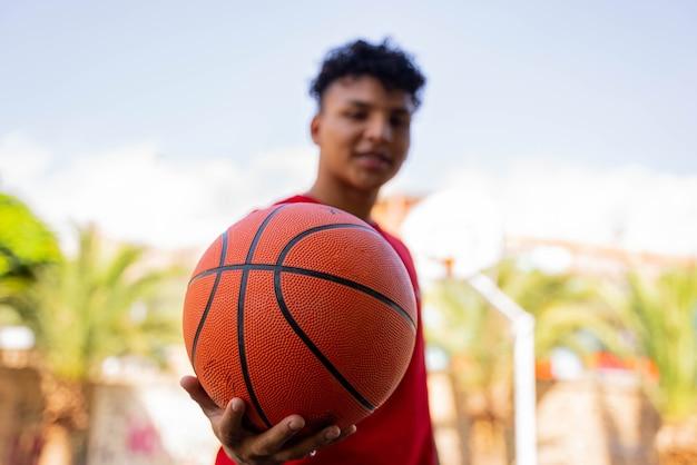 Menino na rua com basquete