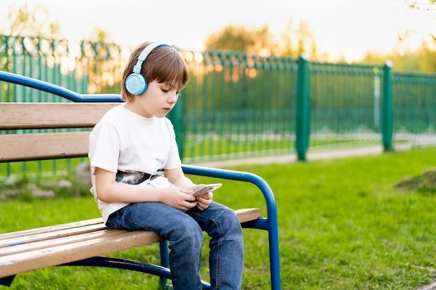 Menino na rua sentado em um banco com fones de ouvido e um telefone