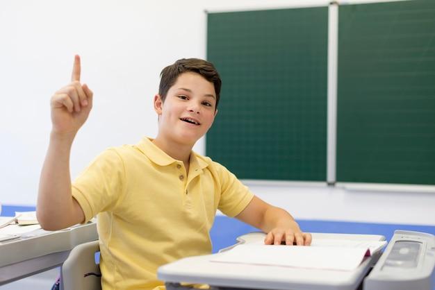 Menino na sala de aula com o dedo levantado