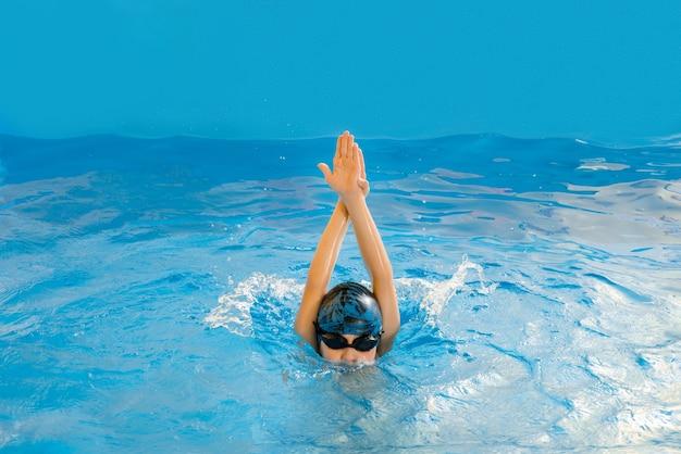 Menino nadando na piscina coberta e se divertindo durante a aula de natação