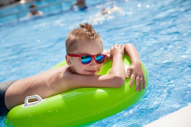 Menino nadando na piscina com grande anel de borracha verde brilhante