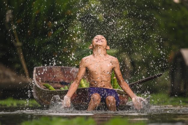 Menino nadando no cannal perto do mercado flutuante de damnoen saduak