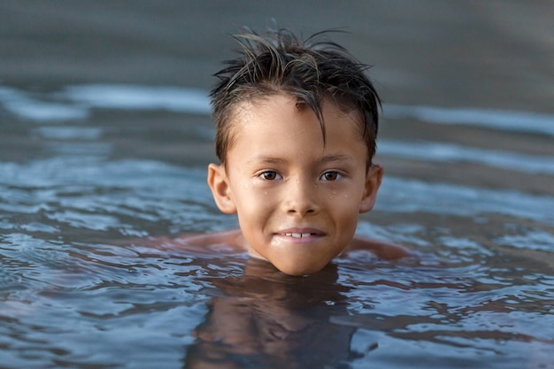 Menino nadar no lago, closeup retrato, verão e infância conceito