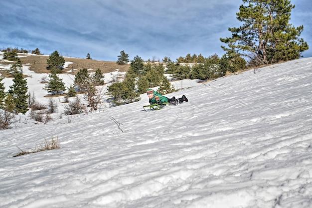 Menino nas montanhas cavalga na neve em um trenó