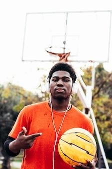 Menino negro afro-americano ouvindo música com fones de ouvido e seu telefone celular depois de jogar basquete em uma quadra urbana.