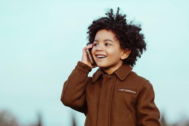 Menino negro com cabelo afro, falando ao celular, sorrindo, desviando o olhar. em um fundo de parque. imagem com copyspace. crianças, smartphones e conceito de pessoas negras