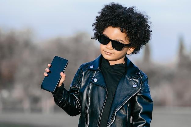 Menino negro com cabelo afro, óculos escuros e jaqueta de couro, mostrando seu smartphone. em um fundo de parque. imagem com copyspace. crianças, smartphones e conceito de pessoas negras
