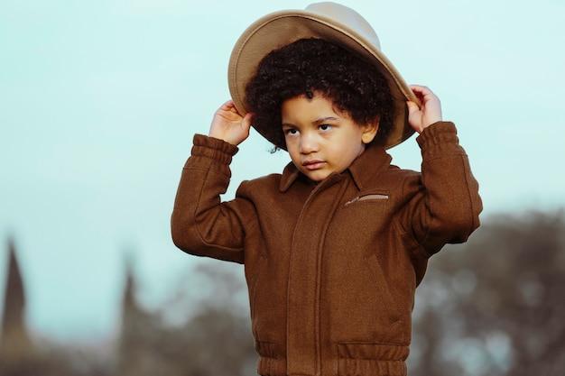 Menino negro com chapéu de cowboy, olhando para longe. em um fundo de parque. . imagem com copyspace. conceito de crianças e negros