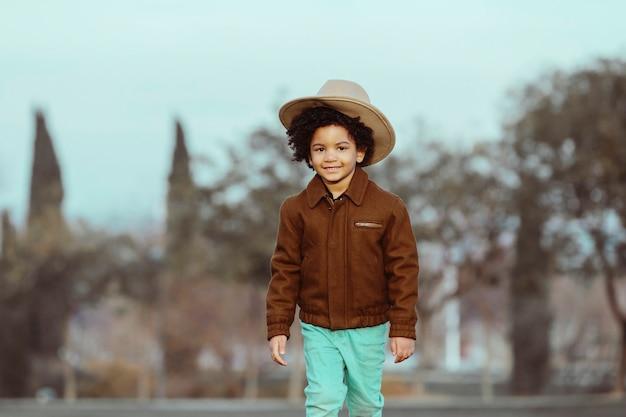 Menino negro com chapéu de cowboy, sorrindo, caminhando. em um fundo de parque. . imagem com copyspace. conceito de crianças e negros