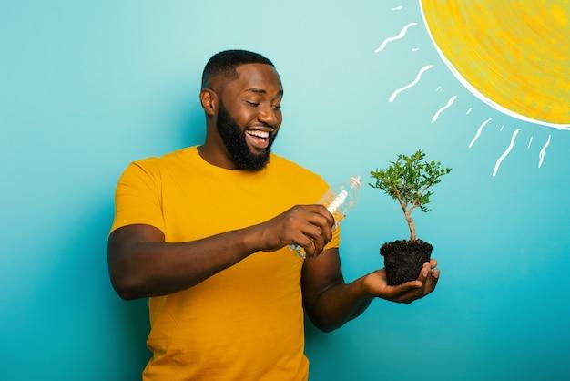Menino negro feliz regando uma pequena árvore pronta para ser plantada