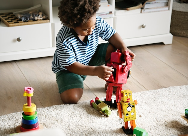 Menino negro jogando robô em casa