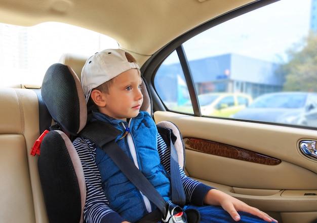 Menino no assento de segurança do carro