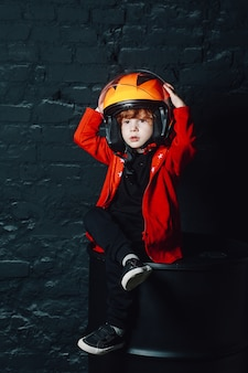 Menino no capacete sob o lustre em uma sala mal iluminada