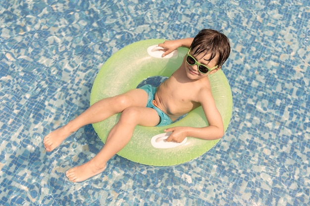 Menino no carro alegórico na piscina
