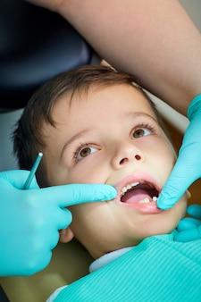 Menino no dentista a recepção abriu a boca em clini