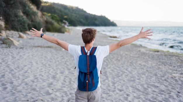 Menino no meio do tiro com mochila na praia