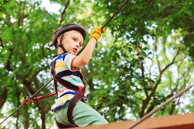Menino no parque da corda do curso no capacete e no equipamento de segurança da montanha.