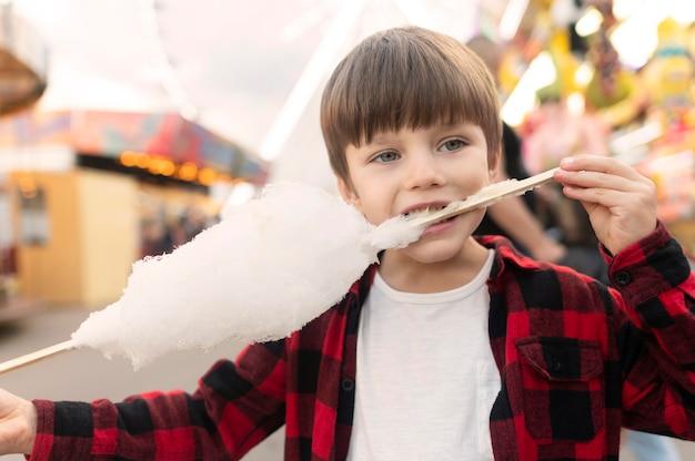 Menino no parque de diversões comendo algodão doce