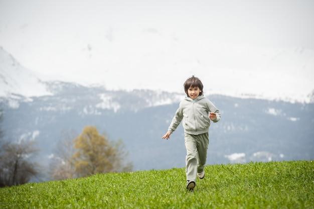 Menino no prado da montanha bonita