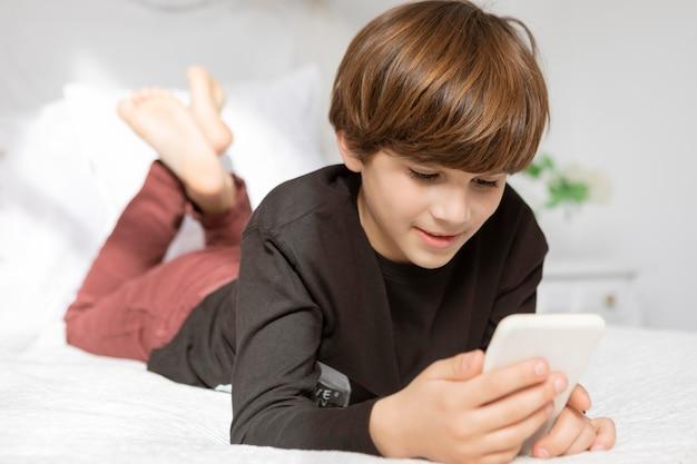 Menino no quarto com telefone