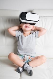 Menino no sofá com fone de ouvido virtual na
