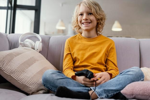 Menino no sofá com joysticks tocando
