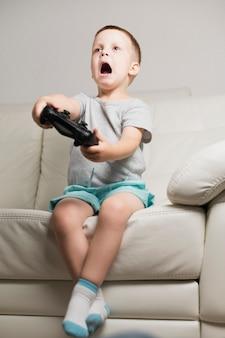 Menino no sofá jogando jogos digitais