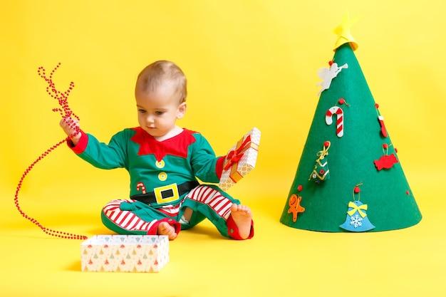 Menino no terno de presente aberto do elfo de papai noel.