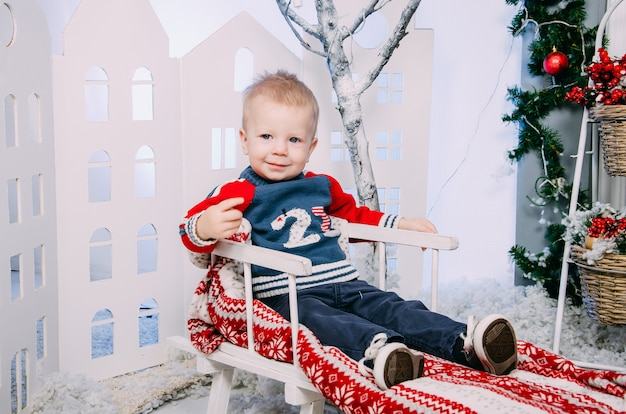 Menino no trenó. garotinho sentado no trenó decorado de madeira, no interior do inverno.
