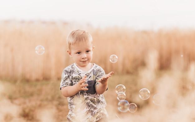 Menino no verão brincando com bolhas de sabão na natureza