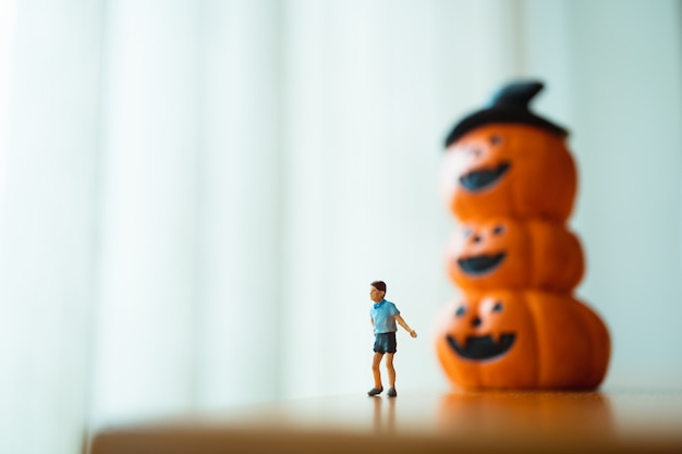 Menino novo diminuto que está com a abóbora do fantasma que usa-se como o conceito da família e do dia das bruxas