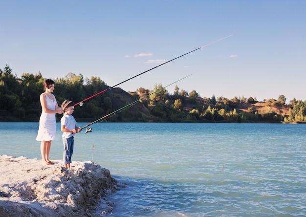 Menino novo e mulheres que pescam em um lago
