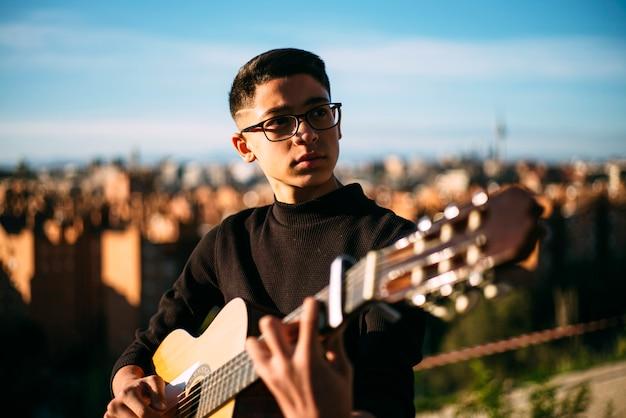 Menino novo que joga a guitarra na cidade do madri, espanha no fundo.