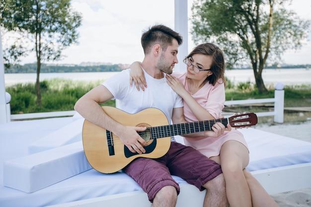 Menino novo que joga a guitarra para sua namorada enquanto ela o abraça