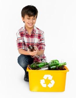 Menino novo que separa garrafas de vidro recicláveis