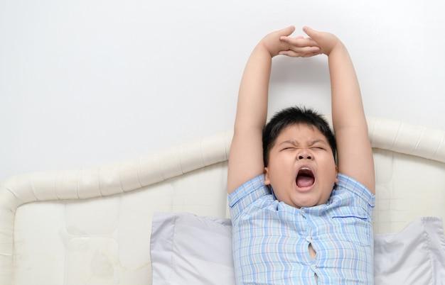 Menino obeso bocejando e alongamento na cama