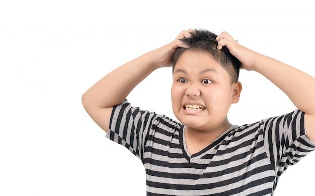 Menino obeso coça o cabelo, isolado no fundo branco,