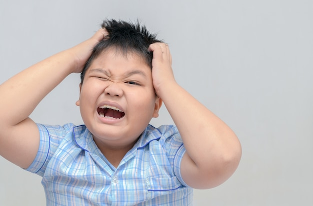 Menino obeso coceira seu cabelo em fundo cinza