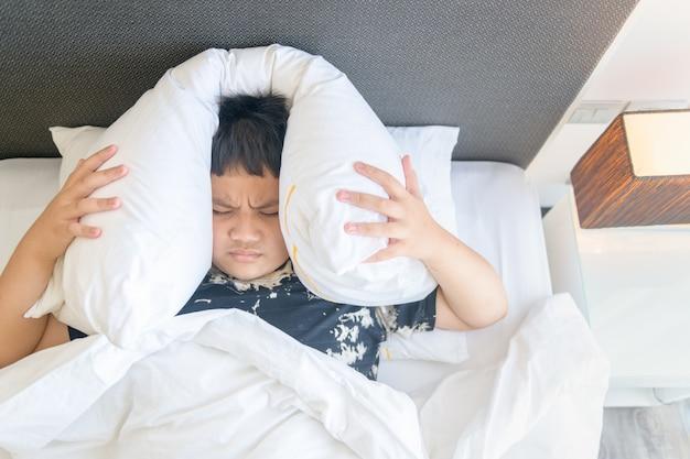 Menino obeso deitado na cama cobrindo a cabeça com o travesseiro por causa do barulho irritante muito alto. criança irritada sofrendo de vizinhos barulhentos, tentando dormir após o sinal de alarme de despertar