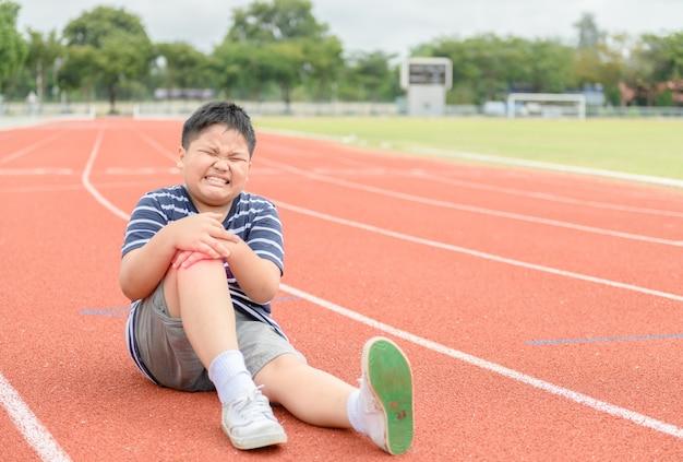 Menino obeso sentindo dor após ter o joelho lesionado